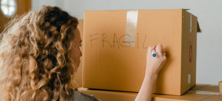 A woman with curly hair writing the word fragile on a moving box.