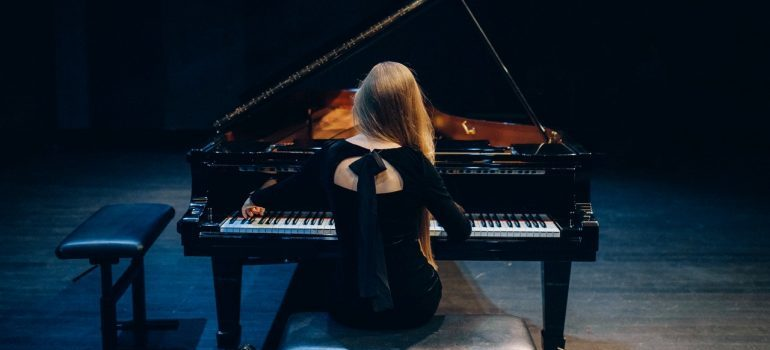 A woman sitting in front of a grand concert piano.